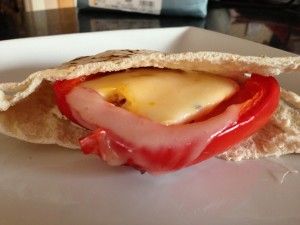 The cheese seals the egg into the pepper cup.